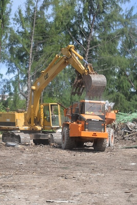 Heavy equipment loads a truck with scrap material