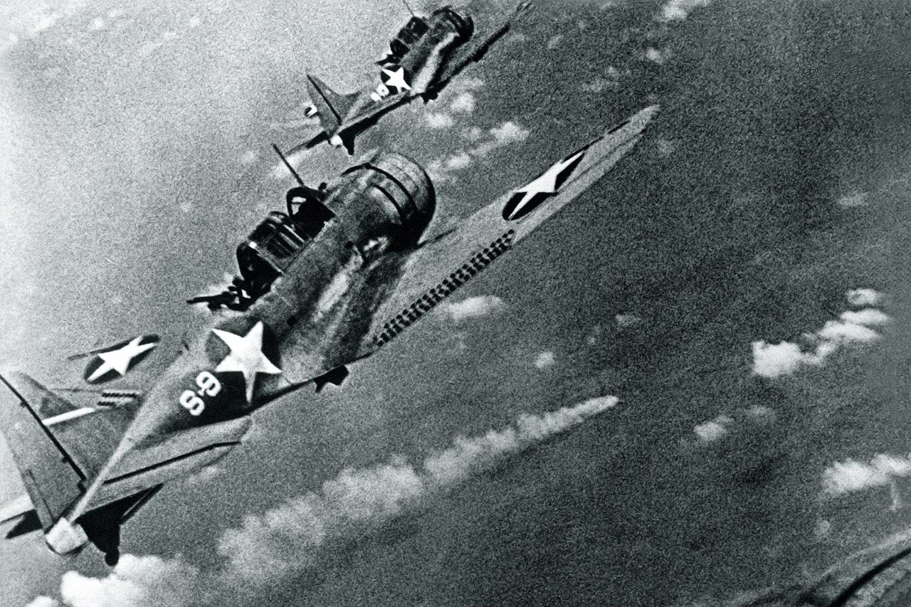 Two dive bombers fly in the sky.