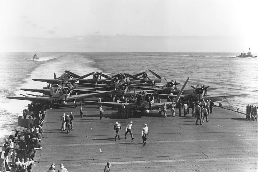 Airplanes on the deck of an aircraft carrier in the middle of the Pacific Ocean.