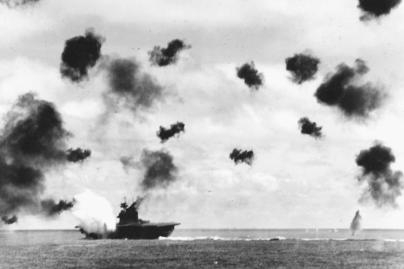 Pufffs of dark smoke dot the sky as bombs fall on a ship.