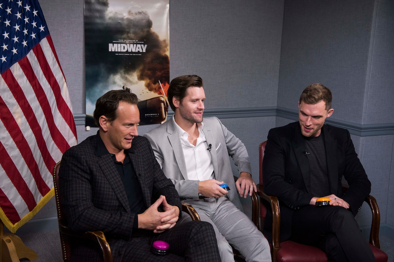"Three men in suits sit in chairs next to one another. In the background is a poster from the movie ""Midway."" A U.S. flag is on the left side of the men."
