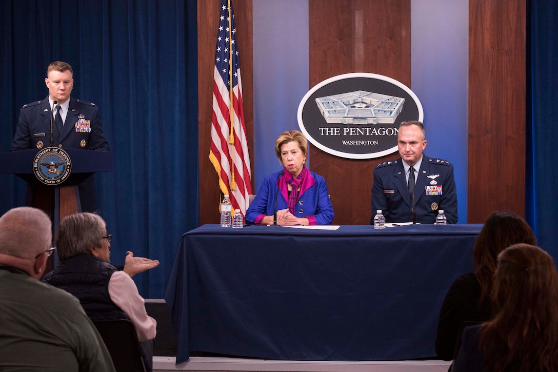 A woman and a man in military uniform sit at a table. Behind them hangs a sign with the words 'The Pentagon ... Washington.'