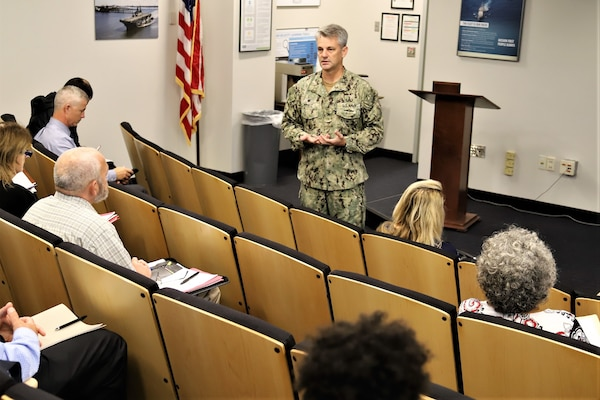 IMAGE: VIRGINIA BEACH, Va. (Oct. 22, 2019) – Capt. Scott Kraft, Naval Surface Warfare Center Indian Head Explosive Ordnance Disposal Technology Division commanding officer, briefs more than 30 safety and occupational health and environmental protection managers at the Naval Warfare Center's two-day Safety and Environmental Face-to-Face Symposium. The managers shared innovative ideas, trends, and information impacting safety, occupational health, and environmental protection at the event hosted by Naval Surface Warfare Center Dahlgren Division Dam Neck Activity.  (U.S. Navy photo by George Bieber/Released)