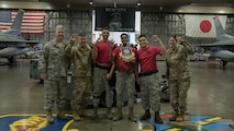 Airmen with the 13th Aircraft Maintenance Unit pose for a photo with their leadership after winning the third quarter load crew competition at Misawa Air Base, Japan, Oct. 25, 2019. The 13th and 14th AMU take part in this friendly competition, ensuring readiness and proper munitions handling while racing against the clock and opponents. The 13th AMU weapons load crew Airmen took home the trophy after being assessed on their performance and weapons load technical abilities. (U.S. Air Force photo by Airman 1st Class China M. Shock)