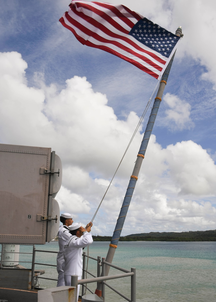 Sailors assigned to the amphibious assault ship USS Boxer (LHD 4) raise the American flag on the fantail after the ship moors at Naval Base Guam.