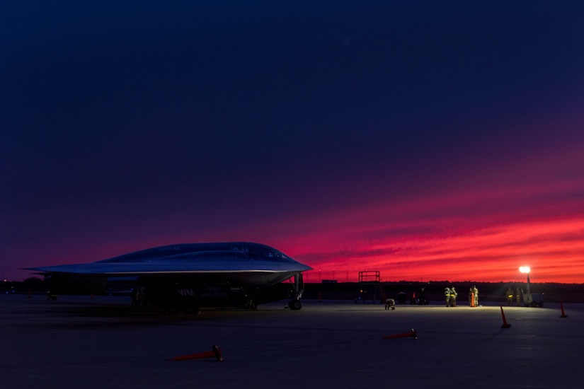 A plane sits parked at night.
