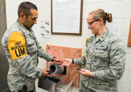 Tech. Sgt. Damien Seelbach, cybersecurity noncommissioned officer in charge, hands 1st Lt. Rachael Burks, cyber operations flight commander, a 9mm bullet from the chamber of a Beretta M9 during the disarming process conducted in the 436th Communications Squadron's arming area, Oct. 24, 2019, on Dover Air Force Base, Del. Both Seelbach and Burks are squadron Unit Marshals. (U.S. Air Force photo by Roland Balik)