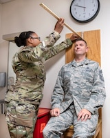 U.S. Air Force Staff Sgt. Ashley Lemonius, 60th Aerospace Medicine Squadron flight operations medical technician, measures the sitting height position of Chief Master Sgt. Derek Crowder, 60th Air Mobility Wing command chief, during a Leadership Rounds visit at Travis Air Force Base, California, Oct. 18, 2019. The Leadership Rounds program provides 60th AMW leadership with an opportunity to interact with Airmen to get a detailed view of each mission performed at Travis AFB. (U.S. Air Force photo by Louis Briscese)