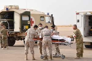 U.S. Air Force and Royal Jordanian Air Force medical teams transport a patient with simulated injuries during a Mass Casualty exercise at the 332d Air Expeditionary Wing, Oct. 16, 2019. The teams trained together to share techniques and break language barriers to operate as a unified multi-lateral team. (U.S. Air Force photo by Tech. Sgt. Andrew Satran)