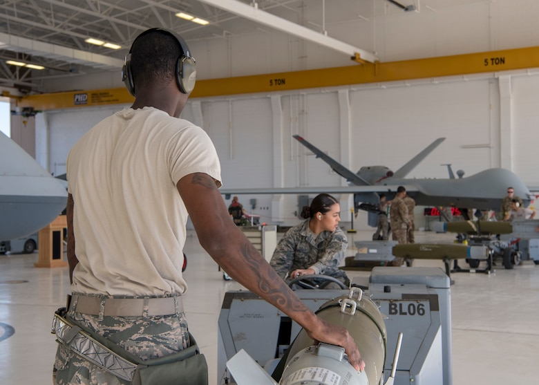 Staff Sgt. Kendrick Johnson, 9th Aircraft Maintenance Unit weapons load crew chief, steadies an inert bomb while Airman 1st Class Jocilyn Rodriguez, 9th Aircraft Maintenance Unit weapons load crew member, directs it to be loaded on an MQ-9 Reaper, Oct. 28, 2019, on Holloman Air Force Base, N.M. Two F-16 Vipers and two MQ-9 Reapers were used to test the loading skills of 12 Airmen during the 2019 third quarter load competition. (U.S. Air Force photo by Airman 1st Class Autumn Vogt)