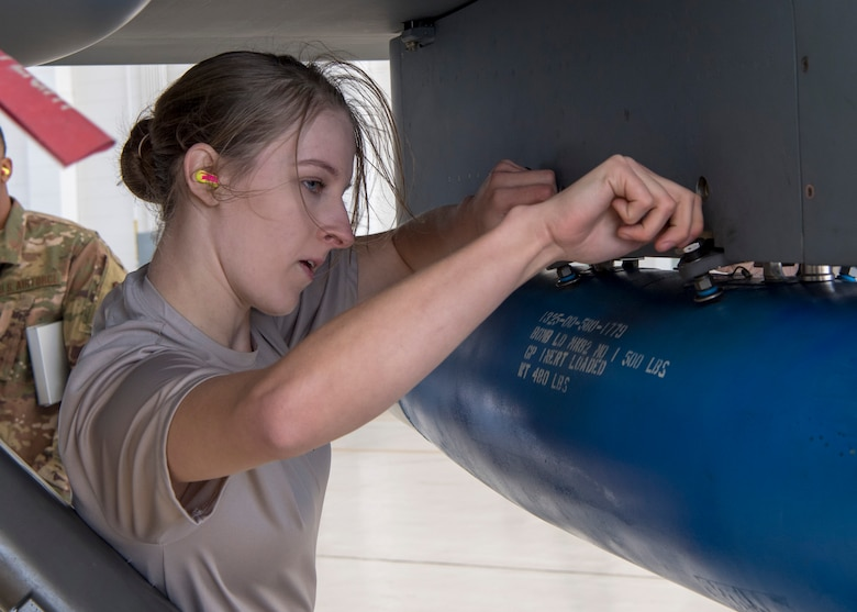Senior Airman Ashley Falls, 29th Aircraft Maintenance Unit weapons load crew member, ensures the inert bomb on an MQ-9 Reaper is secure during a load competition, Oct. 28, 2019, on Holloman Air Force Base, N.M. Two F-16 Vipers and two MQ-9 Reapers were used to test the loading skills of 12 Airmen during the 2019 third quarter load competition. (U.S. Air Force photo by Airman 1st Class Autumn Vogt)