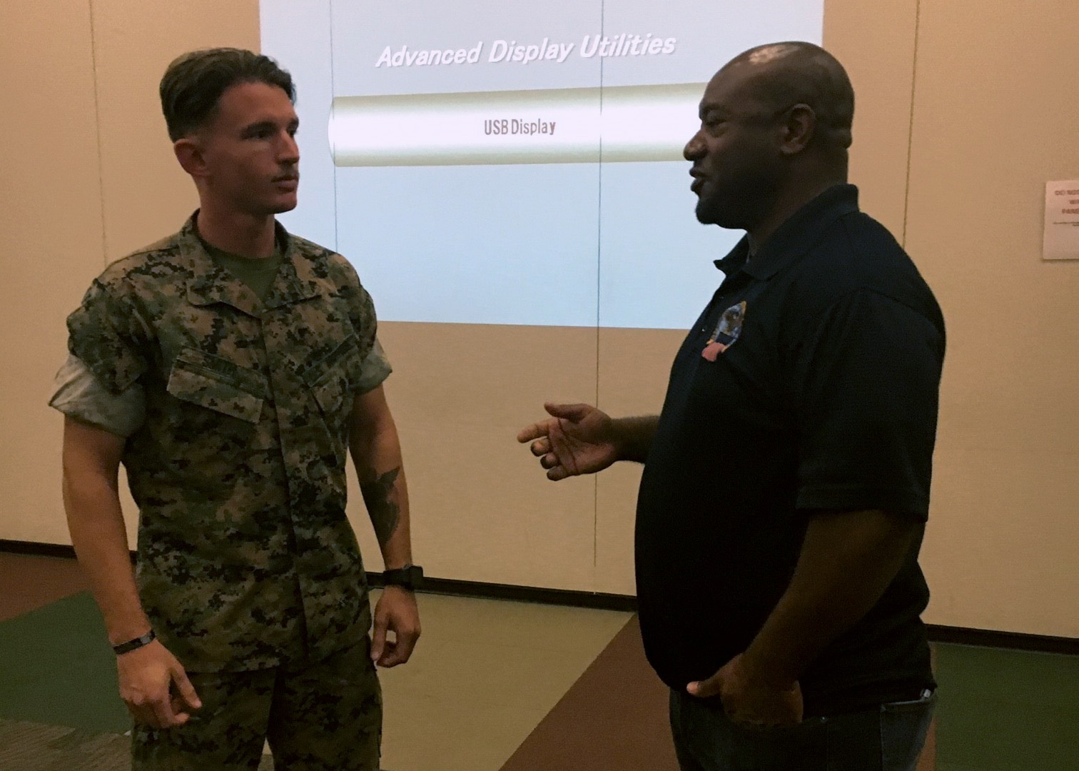 A person in a Marine uniform talks with a Civilian employee.