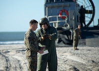 A U.S. Marine 2nd Marine Logistics Group, speaks with a Sailor from Landing Craft, Air Cushion (LCAC) 69 and 53, assigned to Assault Craft Unit (ACU) 4, during Type Commander Amphibious Training (TCAT) 20.1 on Onslow Beach, Camp Lejeune, North Carolina, Oct. 21-26, 2019. TCAT is a mobility exercise ashore in order to gain the requisite skills and experience to integrate with the U.S. Navy in follow on exercises and real-world operations.