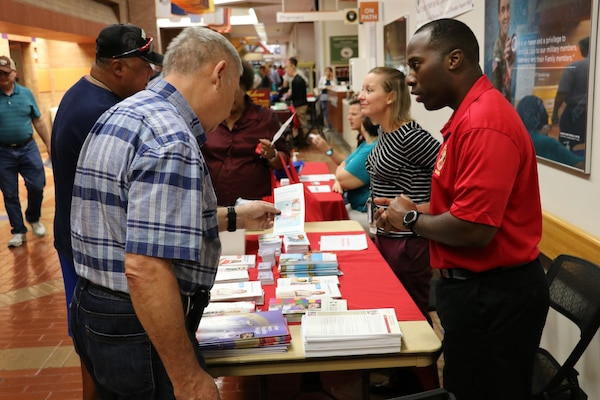 U.S. Air Force Capt. Derrick Wells, executive officer, Department of Medicine, Brooke Army Medical Center (right) hands out information brochures to patrons during Joint Base San Antonio's Military Retiree Appreciation Day Oct. 19, hosted by BAMC.