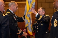 Gen. Gustave F. Perna, U.S. Army Materiel Command commanding general, center left, passes the U.S. Army Financial Management Command colors to Brig. Gen. Mark S. Bennett, USAFMCOM commanding general, during a ceremony at the Indiana War Memorial in Indianapolis, Oct. 25, 2019. Bennett took command from Maj. Gen. David C. Coburn, far left, and will work with Command Sgt. Maj. Courtney M. Ross, USAFMCOM senior enlisted advisor, far right, to lead the command. (U.S. Army photo by Mark R. W. Orders-Woempner)