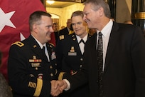 Greg Schmalfeldt, Defense Finance and Accounting Service Indianapolis director and Army client executive, right, congratulates Brig. Gen. Mark S. Bennett shortly after Bennett took command of the U.S. Army Financial Management Command during a ceremony at the Indiana War Memorial in Indianapolis, Oct. 25, 2019. USAFMCOM's mission is to conduct enterprise-level financial operations and provide technical coordination for finance and comptroller units and commands across the Army in order to ensure the effective implementation of policies and programs to support, optimally resourcing the Army. (U.S. Army photo by Mark R. W. Orders-Woempner)