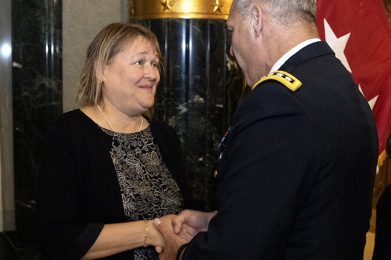 Gen. Gustave F. Perna, U.S. Army Materiel Command commanding general, presents a coin to Yvonne Bennett welcoming her to the AMC family shortly after her husband, Brig. Gen. Mark S. Bennett, took command of the U.S. Army Financial Management Command during a ceremony at the Indiana War Memorial in Indianapolis, Oct. 25, 2019. The change of command was the first formal event for USAMCOM since its move under AMC earlier in the month. (U.S. Army photo by Mark R. W. Orders-Woempner)