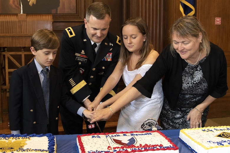 Brig. Gen. Mark S. Bennett, U.S. Army Financial Management Command commanding general, cuts a cake with his son, Matthew, his daughter, Allyson, and his wife, Yvonne shortly after he took command during a ceremony at the Indiana War Memorial in Indianapolis, Oct. 25, 2019. The cake was decorated with a U.S. Army Materiel Command patch symbolizing USAFMCOM's move under AMC earlier that month. (U.S. Army photo by Mark R. W. Orders-Woempner)