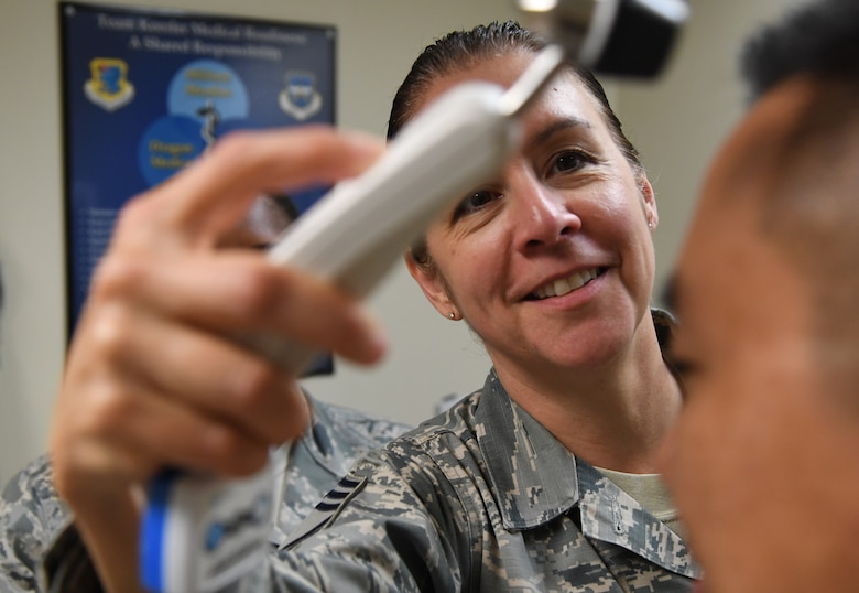 """U.S. Air Force Chief Master Sgt. Paula Eischen, 81st Medical Group superintendent, checks a patient's temperature while visiting the Base Operation Medicine Cell inside the Keesler Medical Center at Keesler Air Force Base, Mississippi, Aug. 22, 2019. The """"Dragon Medic Experience"""" allowed the 81st MDG leadership to work side-by-side with group medics in order to understand the challenges and barriers they may face while providing care. It also allowed them to see first-hand the great ideas that the staff has implemented to focus on the patient experience. This experience helps us cultivate an environment where senior leadership has direct engagement and connection with our front line medics who strive to deliver outstanding care. (U.S. Air Force photo by Kemberly Groue)"""