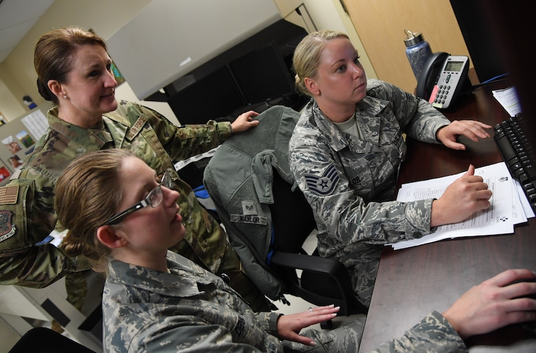 """U.S. Air Force Staff Sgts. Ashley Dena and Hannah Naylor, 81st Aerospace Medicine Squadron medical technicians, brief Col. Beatrice Dolihite, 81st Medical Group commander, on the medical clearance process at the Base Operation Medicine Cell inside the Keesler Medical Center at Keesler Air Force Base, Mississippi, Aug. 22, 2019. The """"Dragon Medic Experience"""" allowed the 81st MDG leadership to work side-by-side with group medics in order to understand the challenges and barriers they may face while providing care. It also allowed them to see first-hand the great ideas that the staff has implemented to focus on the patient experience. This experience helps us cultivate an environment where senior leadership has direct engagement and connection with our front line medics who strive to deliver outstanding care. (U.S. Air Force photo by Kemberly Groue)"""
