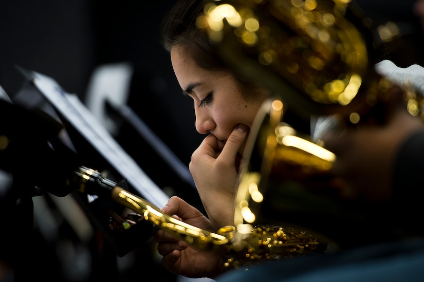 Close-up profile photo of a saxophonist's face as she rests.