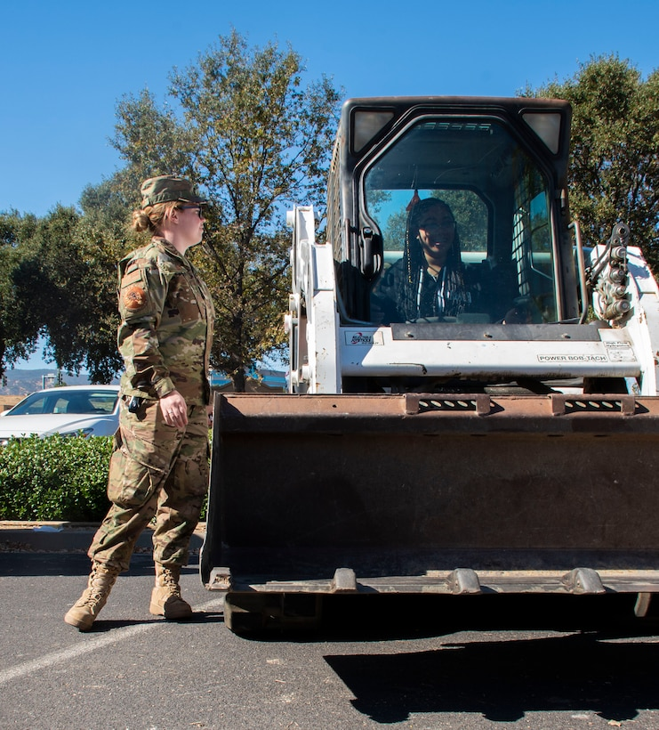 U.S. Air Force Senior Airman Megan Lanzer, left, 60th Civil Engineer Squadron pavements and equipment journeyman, teaches Aniyah Blanche, a student with the Inspire: Dreams Start Now exhibit, how to operate a Bobcat Oct. 22, 2019, at Ulatis Community Center, Vacaville, California.