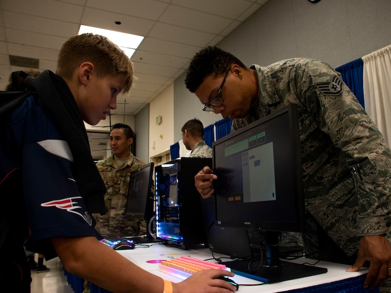 Ryan Duncan, left, an eighth grade student attending the Inspire: Dreams Start Now exhibit, does a coding challenge with U.S. Air Force Staff Sgt. Marcus Larue, 60th Communications Squadron cyber security technician at Travis Air Force Base, California, Oct. 22, 2019, at Ulatis Community Center, Vacaville, California.