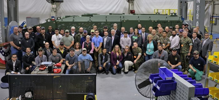 Representatives from Program Manager Advanced Amphibious Assault at Program Executive Officer Land Systems, Marine Corps Combat Development Command, Combat Development and Integration and 3rd Assault Amphibian Battalion pose in front of an unfinished Amphibious Combat Vehicle with the manufacturing workforce in York, Pennsylvania, on Oct. 16, 2019. (Courtesy Photo)