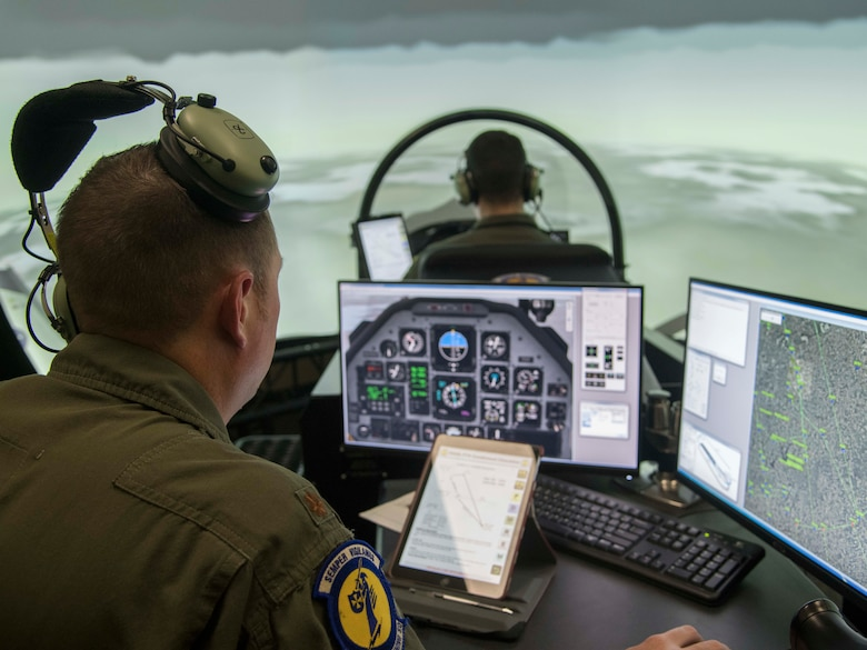 An instructor pilot sits at a console with two monitors that depict cockpit instruments on the left screen and a map of Randolph Air Force Base on the right. Directly infront of him is a simulator cockpit occupied by a student pilot.