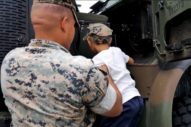 海兵隊の大型トラックに乗り込もうとする児童に手を差し伸べる海兵隊員。沖縄県浦添市にある米軍基地で10月26~27日、フェスティバルが開催され、約23000人の日米の観客が会場に足を運びました。