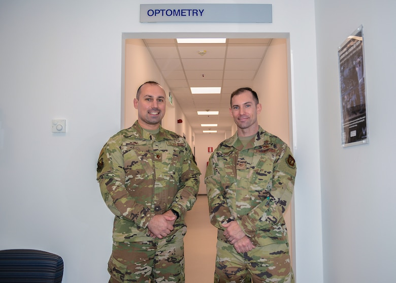 U.S. Air Force Maj. Matthew Tholl, 31st Aerospace Medicine Squadron optometry flight commander (left) and U.S. Air Force Tech. Sgt. Joel Ives, 31st Aerospace Medicine Squadron optometry flight chief (right) pose in front of the entrance of the new Optometry office at Aviano Air Base, Italy, Oct. 30, 2019. Optometry treats up to 25 patients every day. (U.S. Air Force photo by Airman Thomas S. Keisler IV)