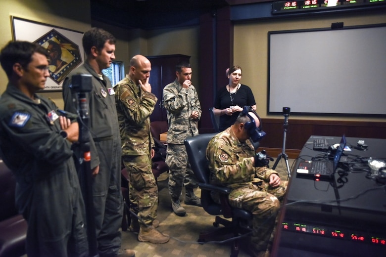 Members of AFWERX and the 189th Airlift Wing Innovation Team watch as Col. Dean Martin, 189th AW commander, tests the virtual reality headset and haptic glove designed to streamline training. (U.S. Air National Guard photo by Master. Sgt. Jessica Roles)