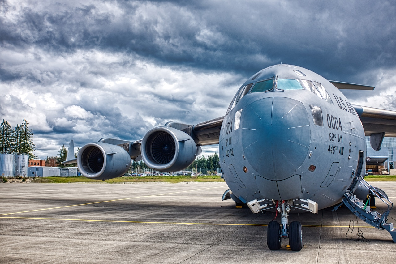 An aircraft sits on a concrete slab. The sky is cloudy and gray.