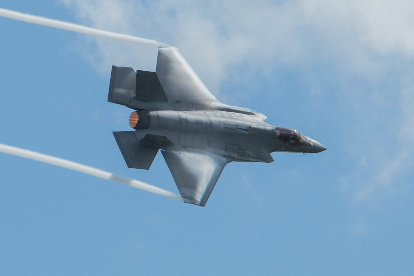 A military fighter aircraft flies across a blue sky.