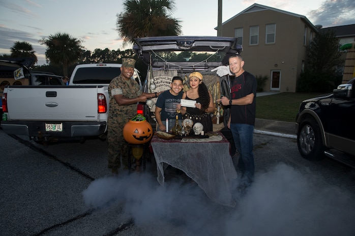 Col. William C. Gray, the 6th Marine Corps District commanding officer, and Sgt. Maj. William Banks III, 6MCD sergeant major, present an award to Gunnery Sgt. Tony J. Hernandez and family during a Trunk-or-Treat competition at 6MCD, MCRD Parris Island, South Carolina, Oct. 28, 2019. (U.S. Marine Corps photo by Sgt. Jorge A. Rosales)