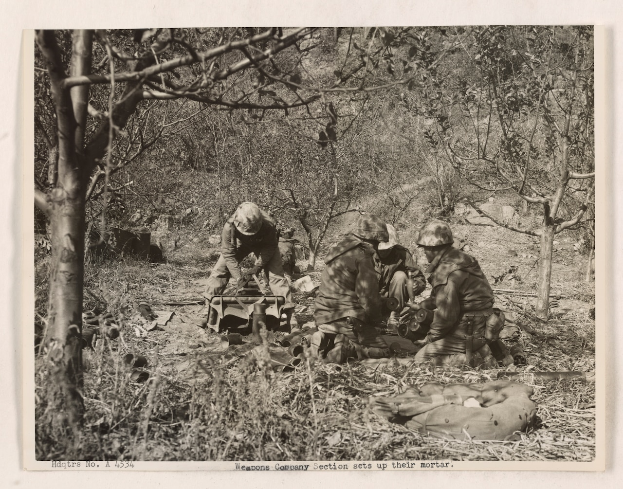 Four Marines work to put together a large gun while surrounded by brush and leafless trees.