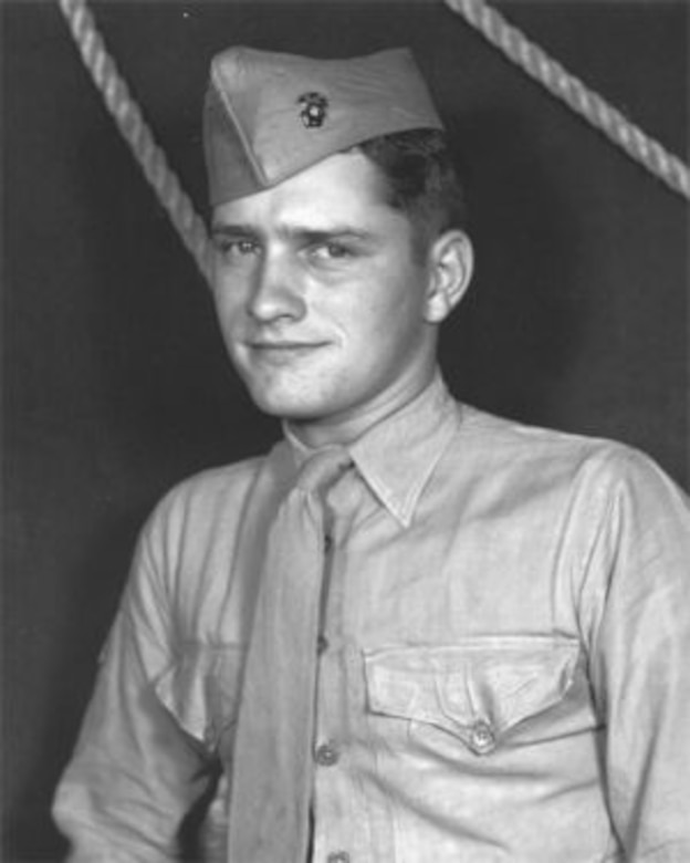 A young man wearing a shirt, tie and cap poses for a photo. Two ropes can be seen behind him.