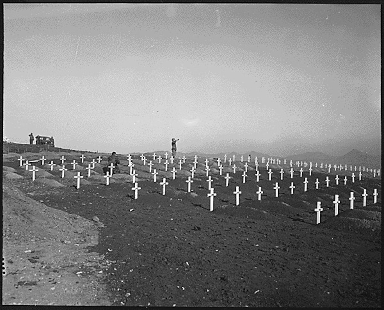 A bugler stands in the distance blowing his bugle in the direction of several rows of crosses at freshly dug graves.