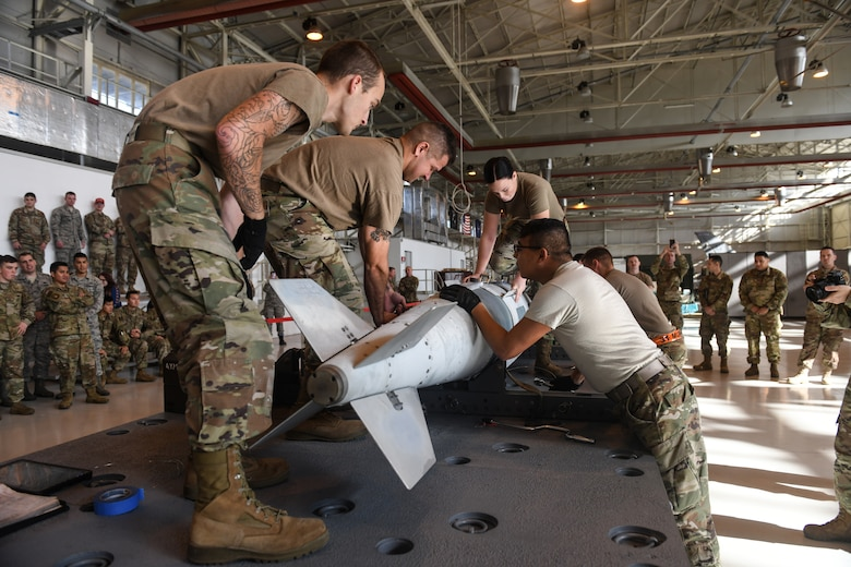 U.S Airmen from the 31st Munition Squadron conduct an inert bomb build at Aviano Air Base, Italy, Oct. 31, 2019. Two teams competed in the final event of Rapid Aircraft Generation and Employment competition. (U.S. Air Force photo by Airman 1st Class Ericka A. Woolever).
