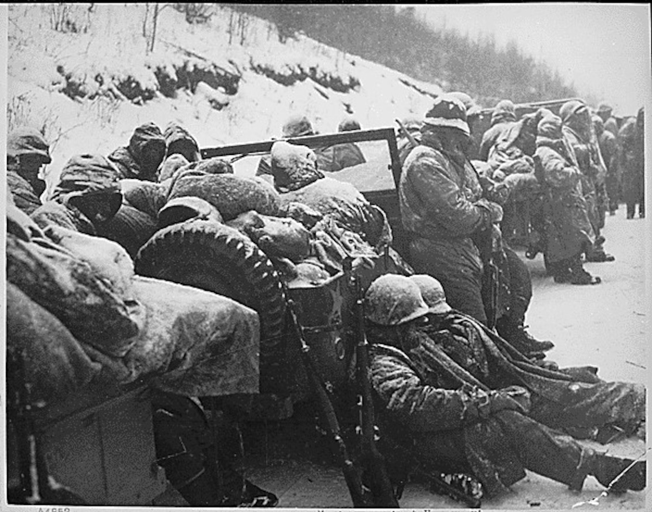 Marines in winter combat gear hold rifles and wait by trucks in the snow by a hill.