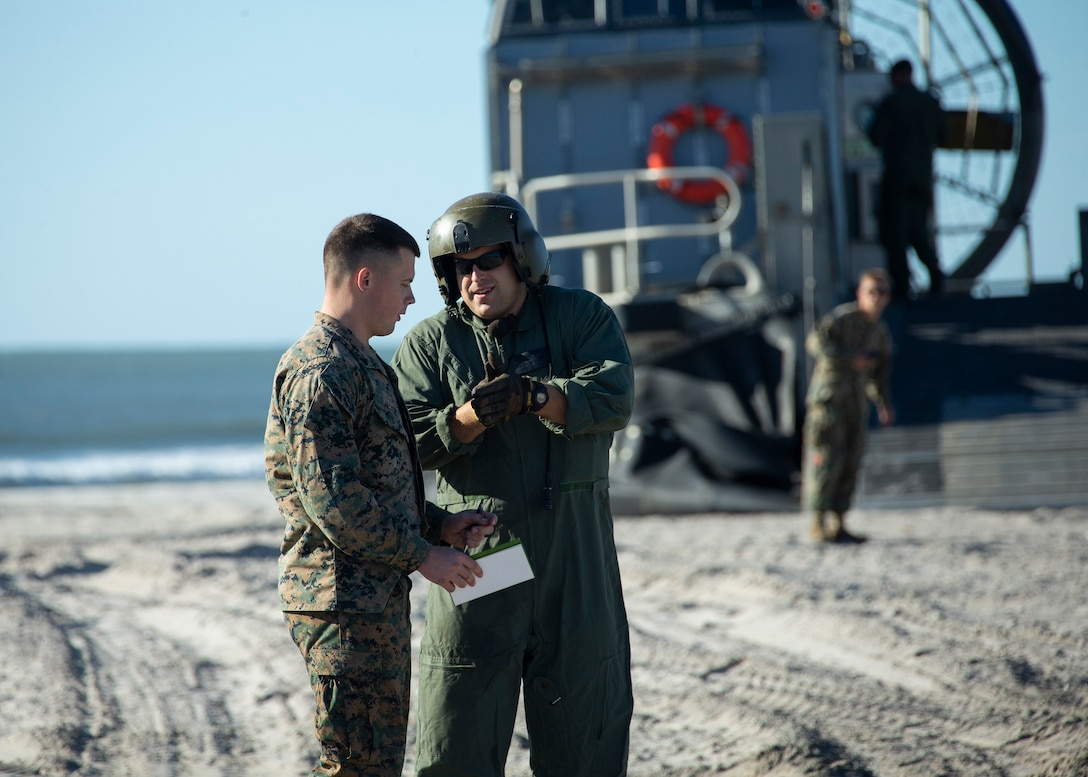 A U.S. Marine with 2nd Transportation Support Battalion, Combat Logistics Regiment 2, 2nd Marine Logistics Group, works with a Sailor from assigned to Assault Craft Unit 4, during Type Commander Amphibious Training 20.1 on Onslow Beach, Camp Lejeune, North Carolina, Oct. 21-26, 2019. TCAT is a mobility exercise ashore in order to gain the requisite skills and experience to integrate with the U.S. Navy in follow on exercises and real-world operations.