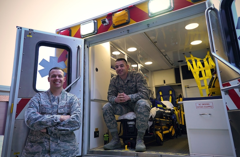 Ambulance service technicians with the 319th Medical Group, Staff Sgt. Jocelin Cartier, left, and Airman 1st Class Michael Nolan, pose for a photo on National First Responders Day, Oct. 28, 2019, on Grand Forks Air Force Base, North Dakota. Cartier and Nolan have served a collective six years in the Air Force, and say they enjoy being able to help people when needed. (U.S Air Force photo illustration by Senior Airman Elora J. Martinez)(This image was emphasized using color filters and vignette.)