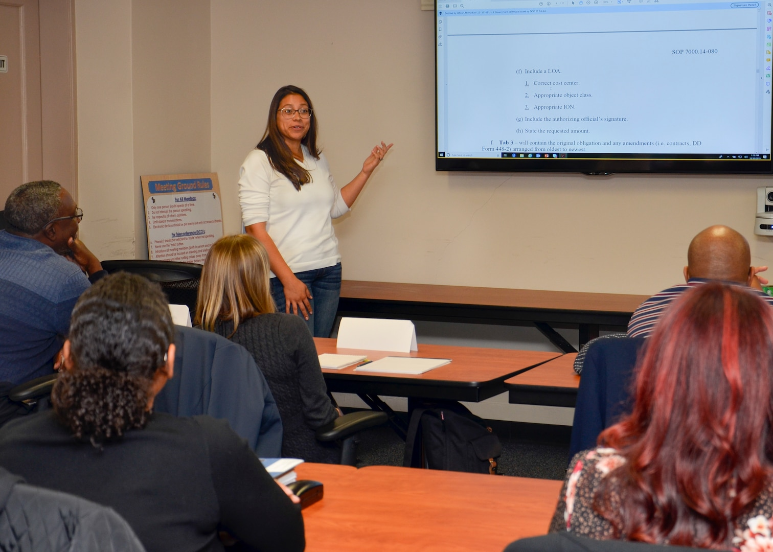 Crystal Leija stands in front of a group of people sitting at tables and leads a workshop topic.