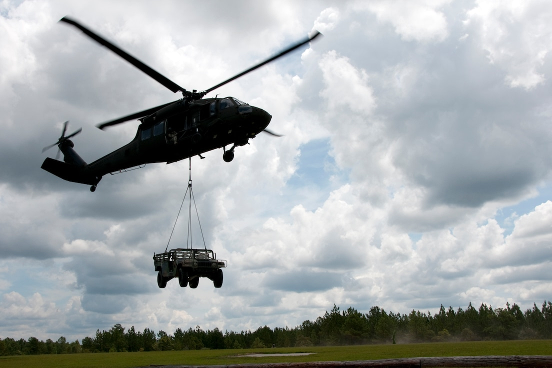 U.S. Army Soldiers with the 351st Aviation Support Battalion, South Carolina Army National Guard, hook up a Humvee to a UH-60 Black Hawk to practice sling load operations in the skies over Columbia, S.C., July 13, 2014.