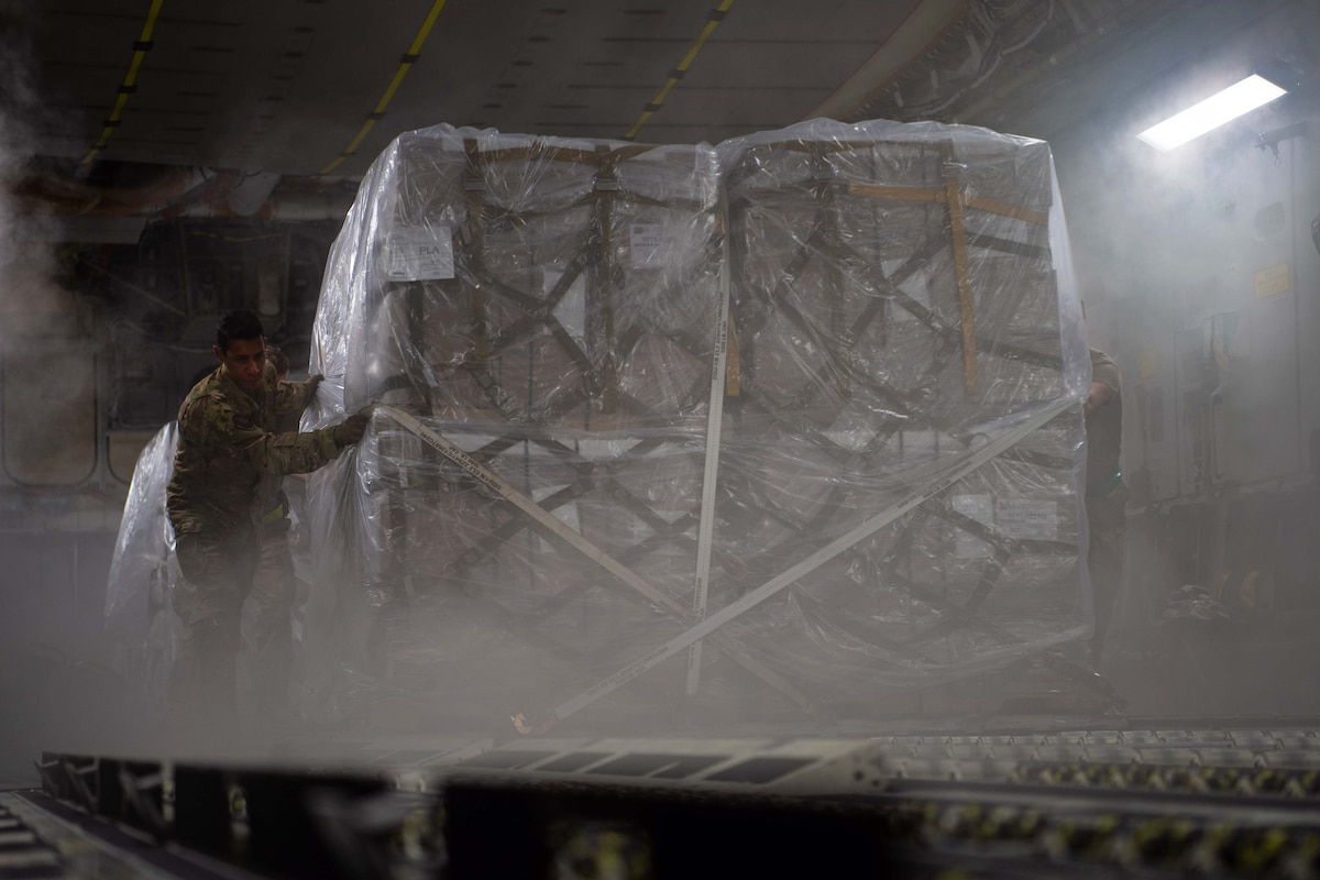 An airman pushes a large pallet inside of an aircraft.