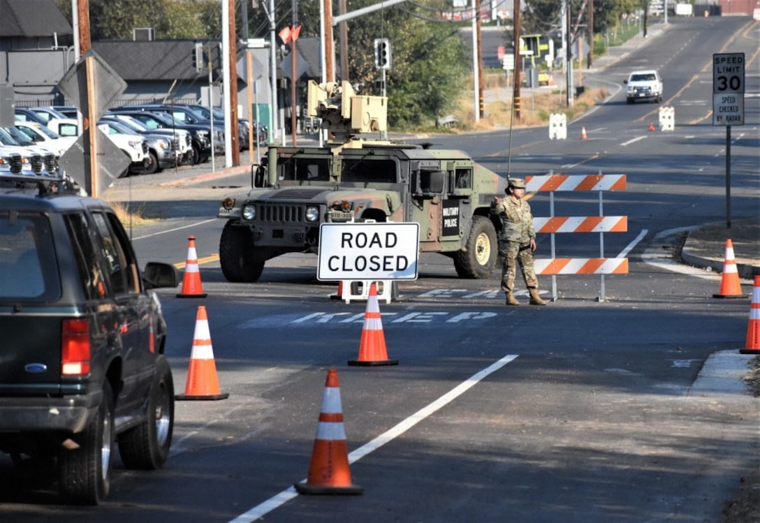 U.S. Army Spc. Maria Medina, a California Army National Guard soldier with Pittsburg-based 870th Military Police Company, blocks traffic from entering Healdsburg, California, Oct. 28, 2019, after an evacuation order was given to multiple towns near the Kincade Fire in Sonoma County. (Photo by Staff Sgt. Amanda Johnson)
