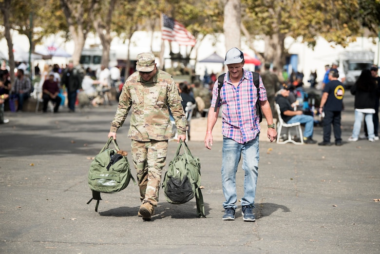 Master Sgt. Travis Martho, 30th Force Support Squadron Airman Leadership School commandant, carries supplies for a veteran during the 2019 Santa Barbara County Veteran Stand Down event Oct. 19, 2019, in Santa Maria, Calif. During the event, veterans were provided with clothes, shoes, a place shower, and other vital supplies and amenities. Veterans were also connected to more than 100 providers to aid them with services such as health care, legal help and vet care for their pets. (U.S. Air Force photo by Airman 1st Class Hanah Abercrombie)