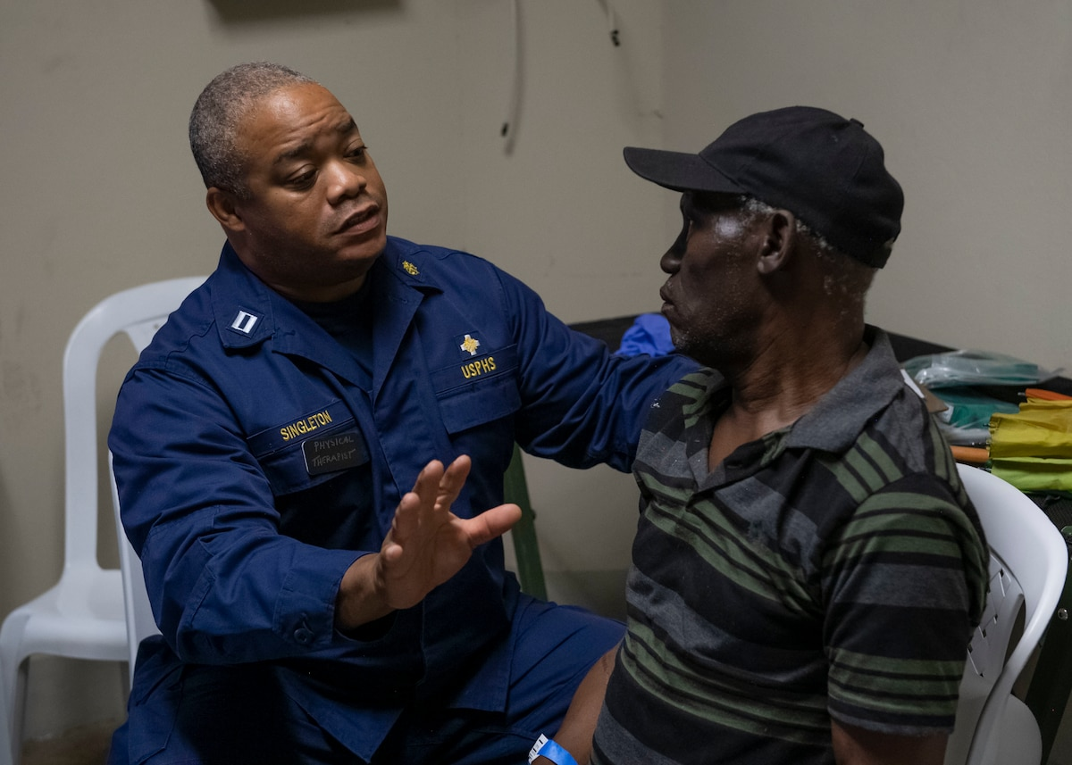 A doctor attached to the hospital ship USNS Comfort (T-AH 20), consults a man about his back pain.