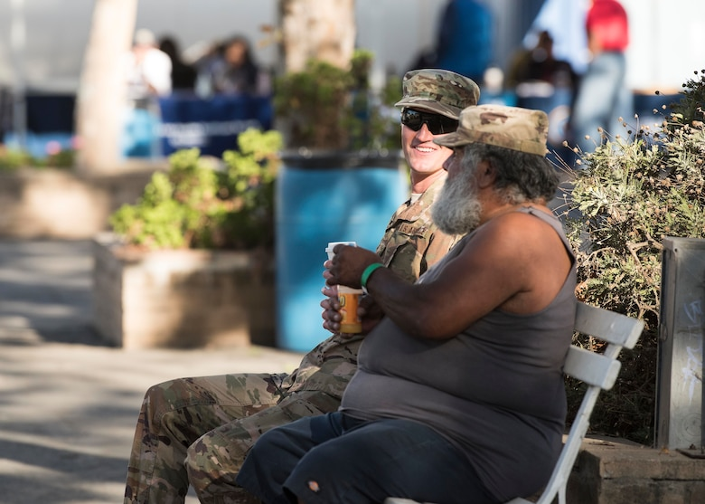 Staff Sgt. Robert Gross, 30th Civil Engineering Squadron utility outage administrator, visits with a homeless veteran during the 2019 Santa Barbara County Veteran Stand Down event Oct. 19, 2019, in Santa Maria, Calif. During the event, Airmen from Vandenberg Air Force Base, Calif. escorted veterans, offering them assistance carrying supplies, and serving as link between prior and current military. (U.S. Air Force photo by Airman 1st Class Hanah Abercrombie)