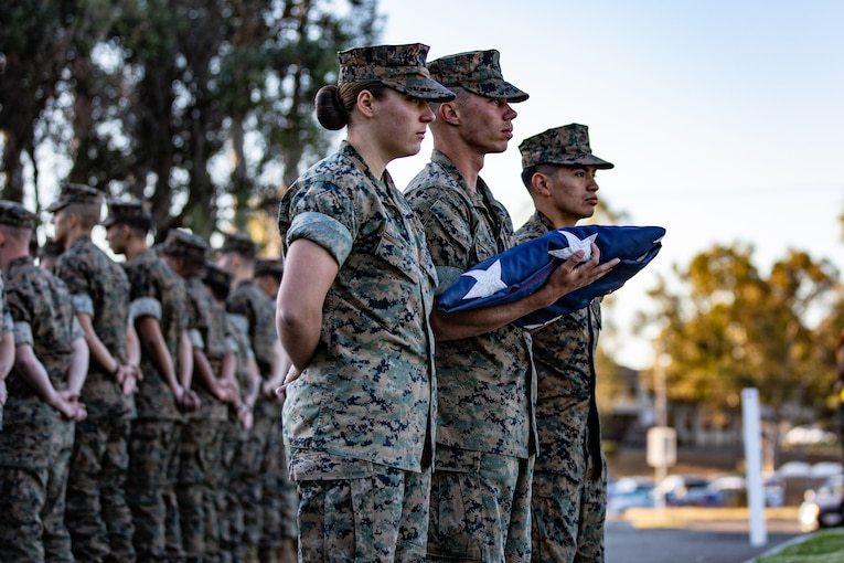 Marines stand in formation as one of them holds a folded American flag.